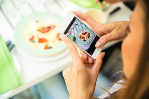 Woman making photo of food on smartphone